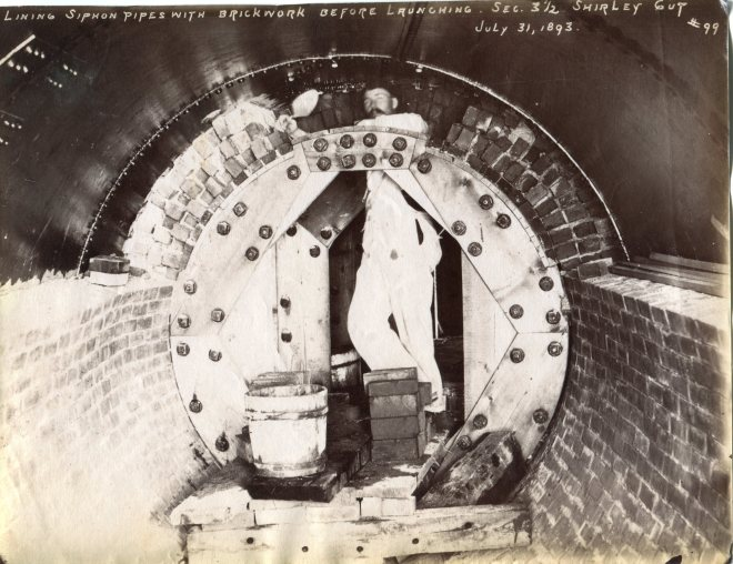 Mason lining the siphon pipes with brickwork before launching, Shirley Gut, July 1893.